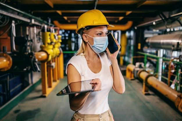Достойная независимая сотрудница в рабочей униформе с защитным шлемом на голове и в маске держит планшет в руках и разговаривает по телефону с начальником, стоя на тэц