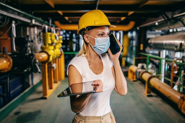 Worthy independent female employee in working uniform with protective helmet on head and with face mask holding tablet in hands and having phone conversation with boss while standing in heating plant