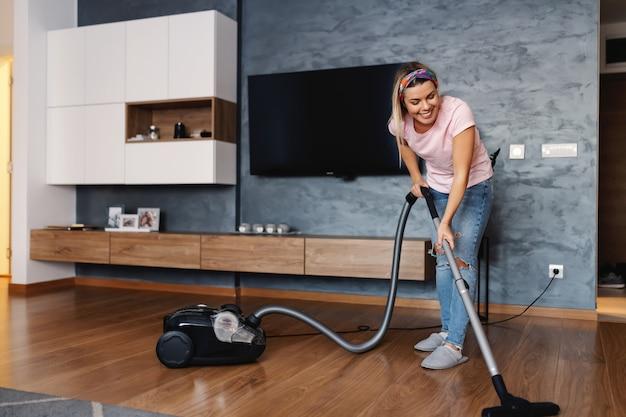 Достойная опрятная улыбающаяся домохозяйка пылесосит пылесосом в гостиной.