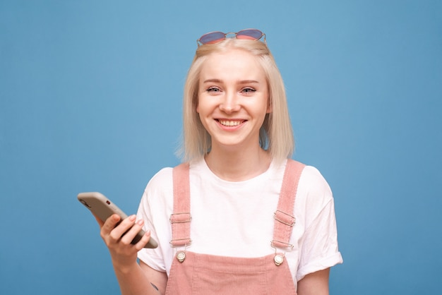 Woteenager on blue, holds a smartphone in her hand