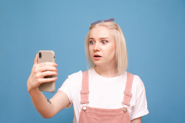 Woteenager with a smartphone in her hand, with astonished face looking at the screen of a phone on blue