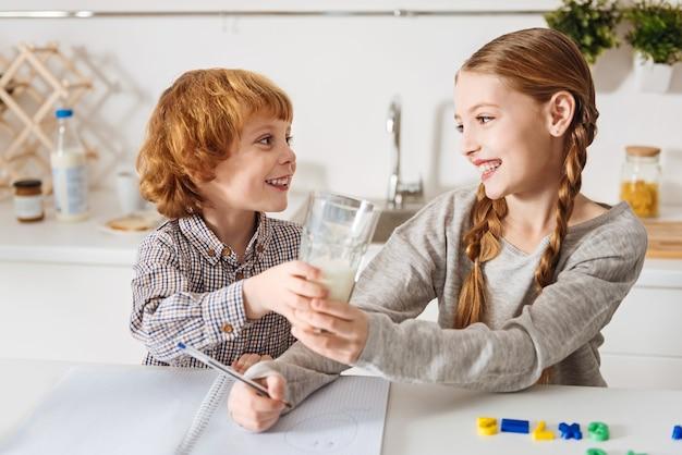 좀 드릴까요? 부엌에서 아침을 즐기고 테이블에 앉아있는 동안 형제에게 우유 한 잔을주는 매력적인 종류의 빨간 머리 소년