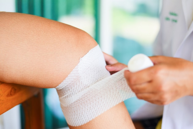 Wound bandaging an injured knee from fall by nurse first aid leg injury health care and medicine