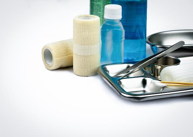 創傷ケアドレッシングセットとステンレスプレート、鉗子、アルコールボトル、粘着性弾性包帯、綿棒、手術用容器。医療機器ツール