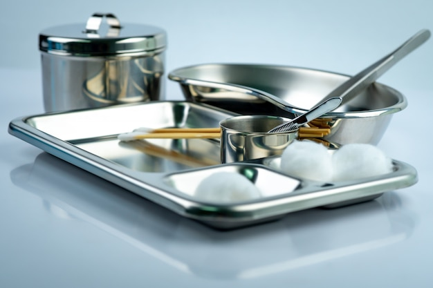 Wound care dressing set on stainless steel plate. white cotton ball, cotton stick, forceps, kidney basin, iodine cup, instruments container  with cover or stainless steel cotton jar set. medical tool.