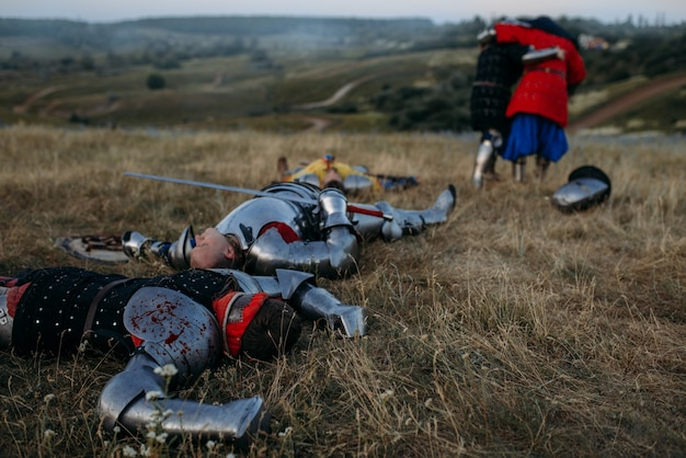 Wounded medieval knights in armor looks at the dead after great battle. armored ancient warrior in armour posing in the field