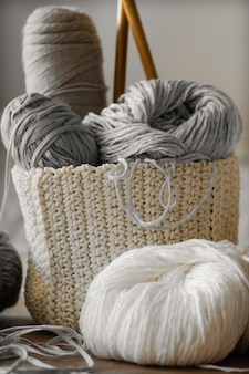 A woven basket with white and gray thread for knitting and knitting needles. white sweaters and yarn for knitting closeup. winter