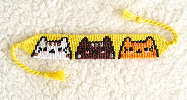 Woven diy friendship bracelet with cats pattern made of embroidery floss