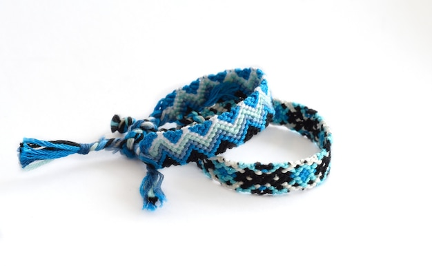 Woven diy friendship bracelets with bright colorful pattern handmade of thread on white