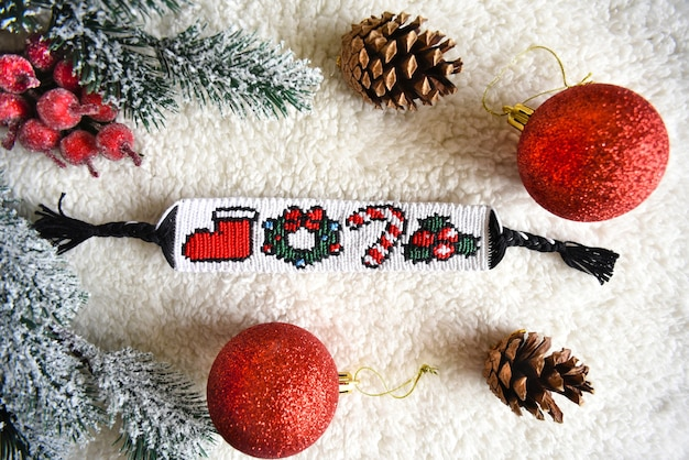Woven friendship bracelet with pattern christmas berry lollipop wreath and santas boot