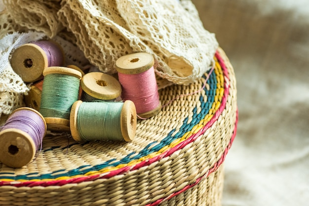 Woven rattan crafts and sewing supply box, wooden spools, rolls of lace, linen
