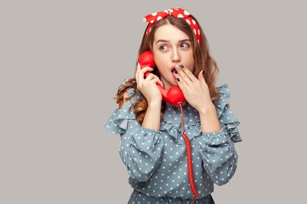 わお!会話に驚いて、口を覆い、ショックを受けた電話の携帯電話を持っている驚いたピンナップガール