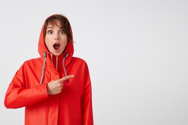 와! 입을 크게 벌리고 빨간 비옷을 입은 깜짝 놀란 짧은 머리 여인이 멋진 소식을 듣는다. 주의를 끌고 복사 공간을 손가락으로 가리 킵니다. 서 있는.