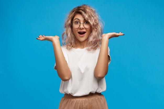 Wow. divertita e affascinata giovane donna europea con capelli voluminosi e disordinati che gesticola emotivamente e tiene la bocca spalancata, non credendo alle tue parole