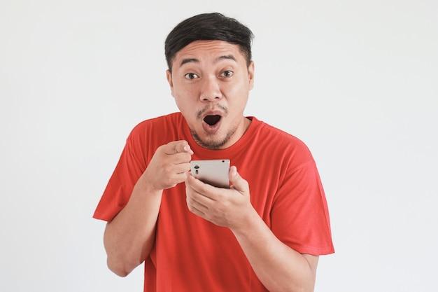 赤いtシャツを着たアジア人男性のすごい、ショックを受けた表情は、彼の手を指してカメラを見ながらスマートフォンで驚きます