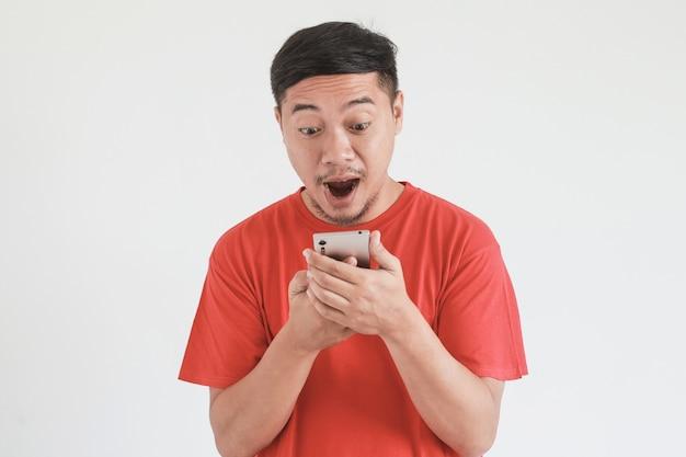赤いtシャツを着たアジア人男性のすごい、ショックを受けた表情がスマートフォンを見て驚かされる