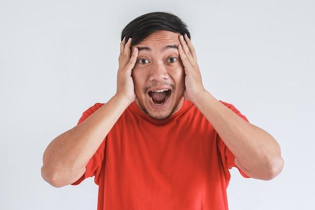 頭を抱えながら赤いtシャツを着たアジア人男性のすごい、ショックを受けた表情