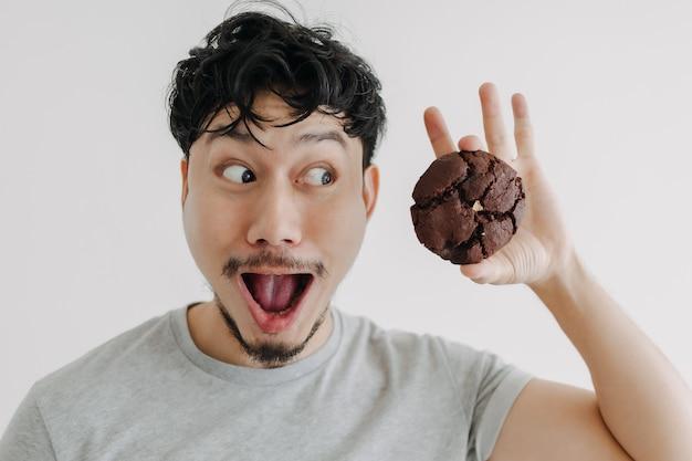 男のすごいショックを受けた顔は巨大なチョコレートクッキーに興奮している
