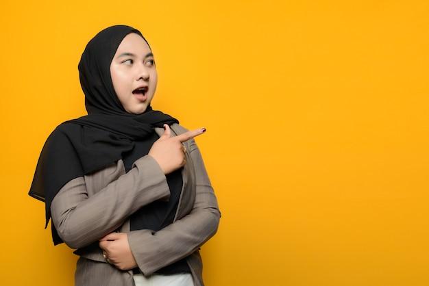 Вау и удивленное лицо азиатской женщины, указывающей на пустое пространство