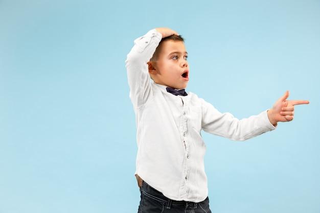 Wow. ritratto frontale a mezzo busto maschio attraente sul backgroud blu dello studio. giovane ragazzo teenager sorpreso emotivo in piedi con la bocca aperta. emozioni umane, concetto di espressione facciale. colori alla moda