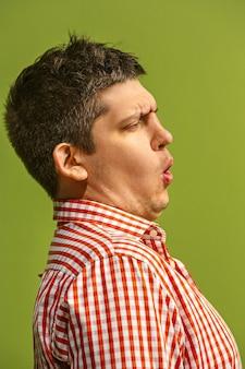 Wow. ritratto frontale a mezzo busto maschio attraente sul backgroud verde dello studio. giovane uomo barbuto sorpreso emotivo in piedi con la bocca aperta. emozioni umane, concetto di espressione facciale. profilo