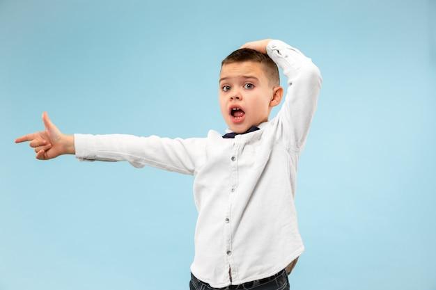 와. 블루 스튜디오 backgroud에 매력적인 남성 절반 길이 전면 초상화. 젊은 감정적 인 놀된 십 대 소년 오픈 입으로 서. 인간의 감정, 표정 개념. 트렌디 한 색상