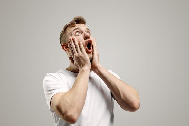와. 회색 스튜디오 backgroud에 매력적인 남성 절반 길이 전면 초상화. 젊은 감정적 인 놀된 수염 난된 남자 입을 열고 서. 인간의 감정, 표정 개념