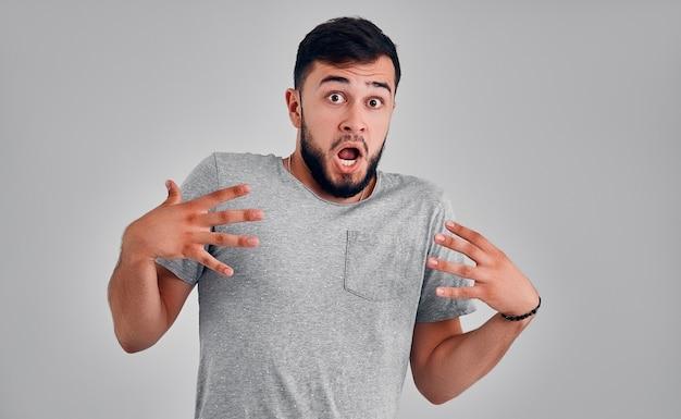 우와. 회색 스튜디오 배경에서 매력적인 남성 절반 길이 전면 초상화. 오픈 입으로 서 있는 젊은 감정 놀된 수염된 남자. 인간의 감정, 표정 개념입니다.