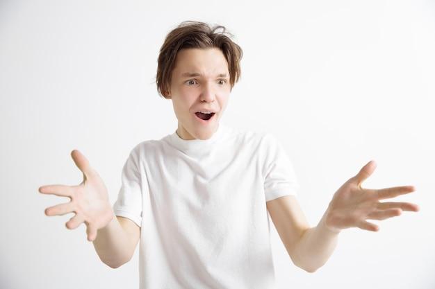 와. 회색 스튜디오 backgroud에 매력적인 남성 절반 길이 전면 초상화. 젊은 정서적 놀란 사람 입을 열고 서. 인간의 감정, 표정 개념