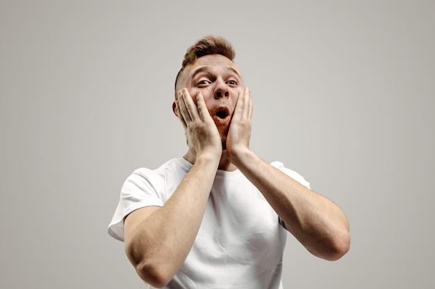 와. 회색 스튜디오에 매력적인 남성 절반 길이 전면 초상화