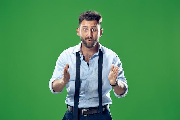 와. 녹색 스튜디오 backgroud에 매력적인 남성 절반 길이 전면 초상화. 뭔가 제시하는 젊은 감정 놀된 수염 된 남자