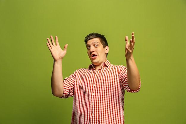 와. 녹색 스튜디오 backgroud에 매력적인 남성 절반 길이 전면 초상화. 입을 벌리고 서있는 젊은 감정 놀란 된 수염 된 남자