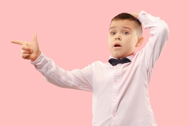 Wow. attractive male half-length front portrait on pink  backgroud. young emotional surprised teen boy standing with open mouth