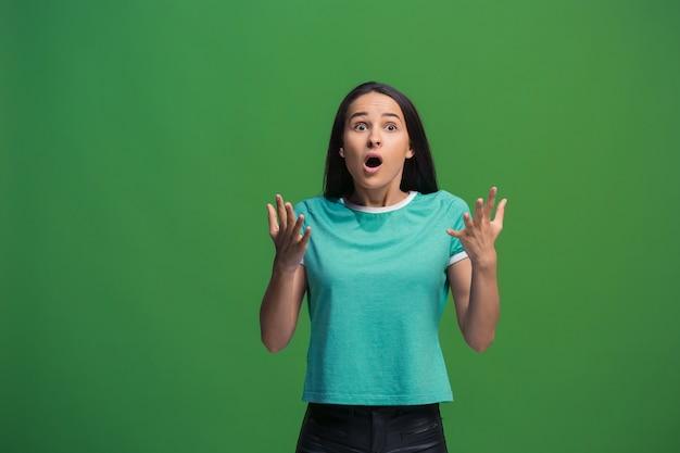 Wow. bello ritratto frontale mezzo busto femminile isolato sul backgroud verde dello studio. giovane donna sorpresa emotiva in piedi con la bocca aperta. emozioni umane, concetto di espressione facciale. colori alla moda