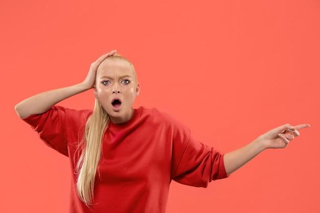 Вау. красивый женский поясной передний портрет изолированный на backgroud студии коралла. молодая эмоциональная удивленная женщина, указывающая налево. человеческие эмоции, концепция выражения лица. модные цвета