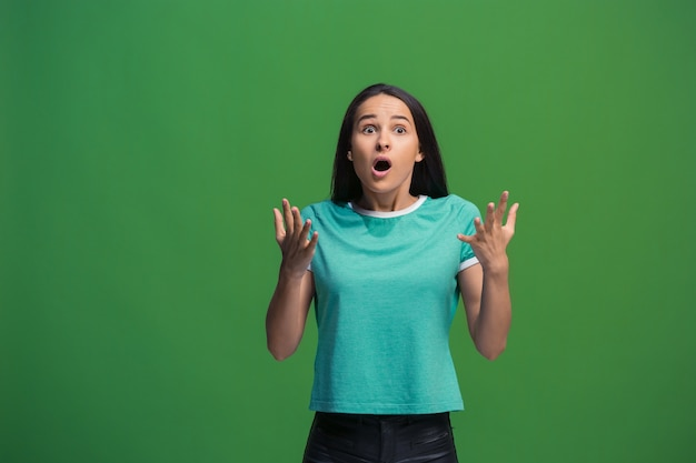 Ух ты. красивый женский поясной передний портрет изолированный на зеленом backgroud студии. молодая эмоциональная удивленная женщина, стоя с открытым ртом. человеческие эмоции, концепция выражения лица. модные цвета