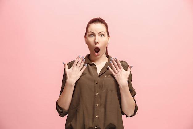 Вот это да. красивый женский поясной передний портрет изолированный на розовом backgroud студии. молодая эмоциональная удивленная женщина, стоя с открытым ртом. человеческие эмоции, концепция выражения лица. модные цвета