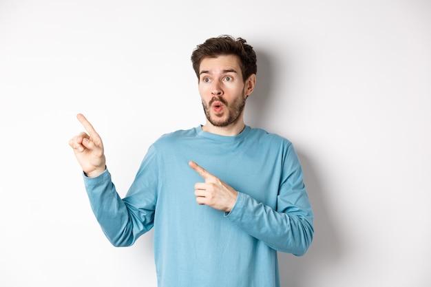 와우 확인해보세요. 젊은 남자가 가리키고 특별 프로모션 제안 또는 할인 흰색 배경에 왼쪽을보고 놀랐습니다.