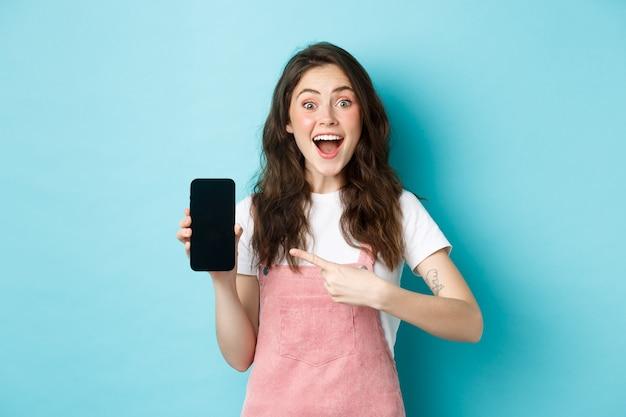 와우 이것을 확인하십시오. 파란 배경에 서서 스마트폰에 로고나 매장 광고를 보여주는 흥분된 예쁜 소녀가 전화 화면을 손가락으로 가리키고 있습니다.