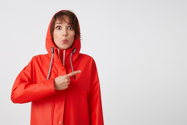 Wow! buone notizie! la signora dai capelli corti stupita con un impermeabile rosso vuole attirare la tua attenzione, punta il dito verso lo spazio della copia. in piedi.