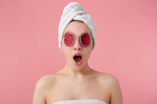 Wow! cool news! young happy amazed girl after spa with a towel on her head and mask on eyes, with wide open mouth and eyes, hears cool news, stands.