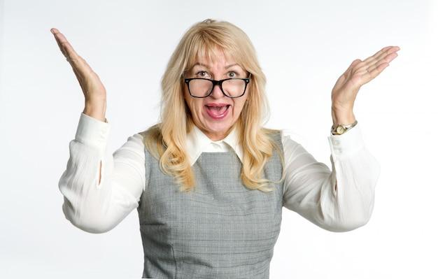 うわー、大喜び!メガネの成熟した女性は、明るい背景に彼女の感情をジェスチャーします。 Premium写真