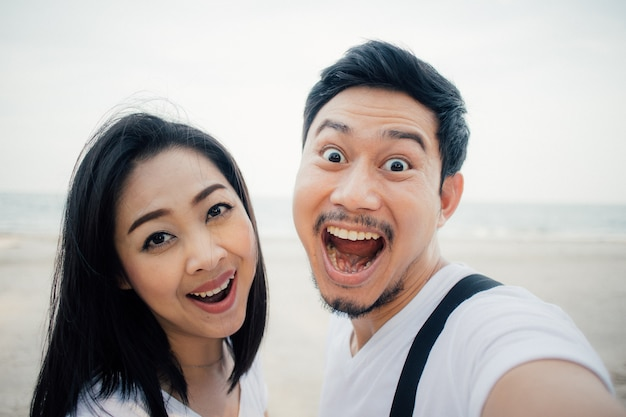 Wow face of couple tourist on romantic beach vacation trip.