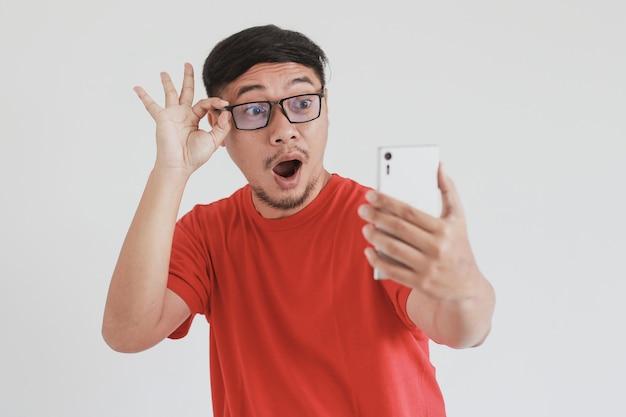 赤いtシャツとメガネをかけたアジア人男性のすごい表情がスマートフォンで見るものに衝撃を与えた