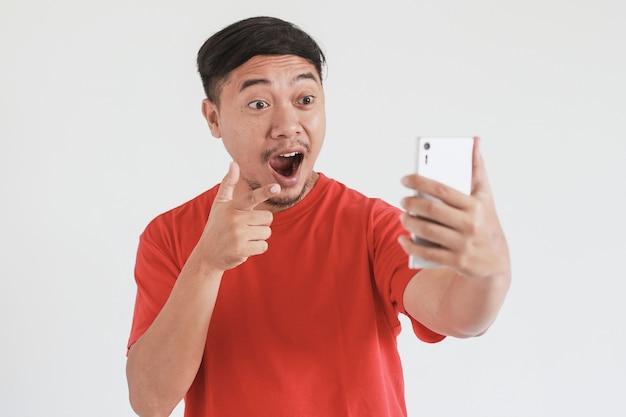 赤いtシャツを着たアジア人男性のすごい表情は、指を指さしながらスマートフォンで見るものに衝撃を与えました