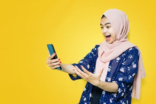 Ух ты, лицо азиатки потрясено увиденным в смартфоне на желтой стене