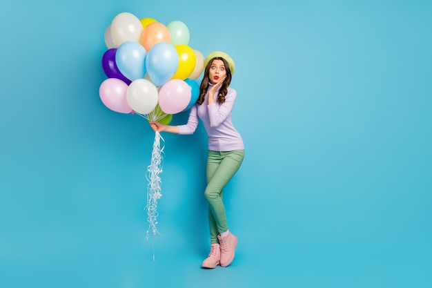 Wow! full length photo of pretty lady hold colorful air balloons friends surprise event party wear purple pullover beret cap green pants footwear isolated blue color wall