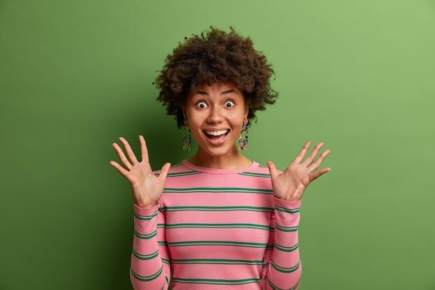 와우! 놀랍게도 과잉 감정을 자극하는 즐거운 곱슬 여자는 손을 들고 행복하게 외치며 믿을 수없는 성공에 놀라고 녹색 벽에 고립 된 캐주얼 스트라이프 스웨터를 입습니다.
