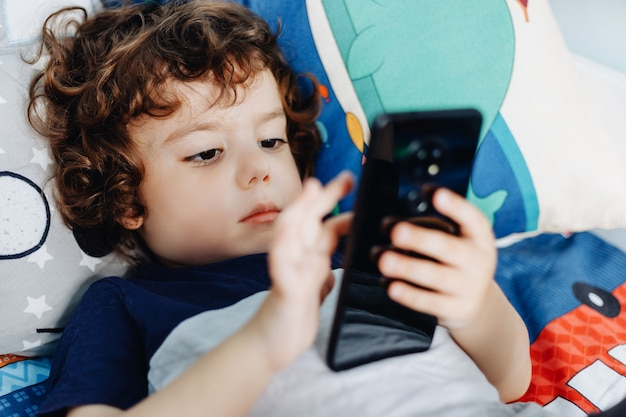 Wow, i like that phone. baby with smartphone. boy sitting in bed and playing with mobile phone. calling my mom. cute little baby holds mobile phone in his hands and looking attentively at screen.