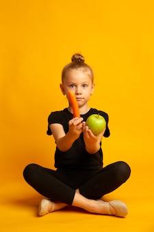 와우 유기농 놀란 어린 소녀 노란색 배경 작은 아이가 유기농 사과와 당근을 들고 천연 유기농 식품 유기농 결정 학교 건강을 먹고 있습니다